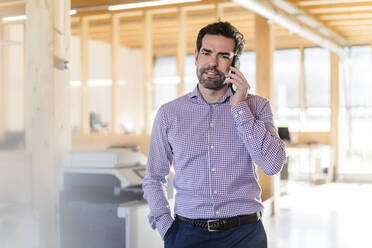 Businessman on the phone in wooden open-plan office - DIGF09522