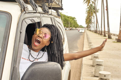 Portrait of screaming woman with dreadlocks leaning out of car window, Maputo, Mozambique - VEGF01693