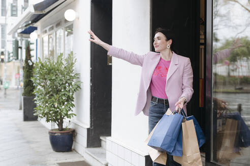 Stylish woman in pink jacket with shopping bags hailing a taxi - VYF00053