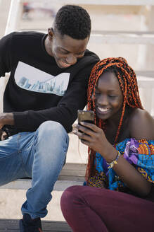 Happy teenage girl and young man sitting on stairs looking at cell phone - MPPF00618