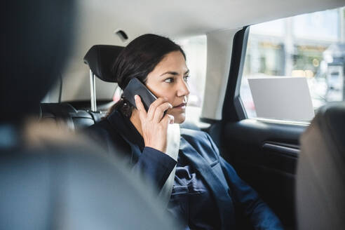 Businesswoman talking through phone while sitting in car - MASF16948