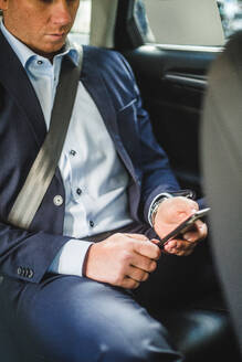 Mature businessman using mobile phone while sitting in car - MASF16954