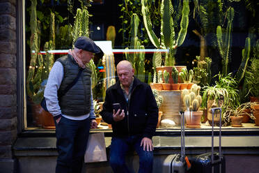 Senior gay couple booking taxi through mobile app while waiting outside plant store at night - MASF17119