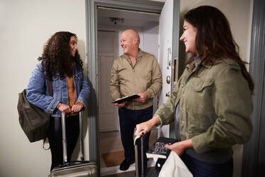 Smiling male owner greeting female guests with luggage at doorway - MASF17128