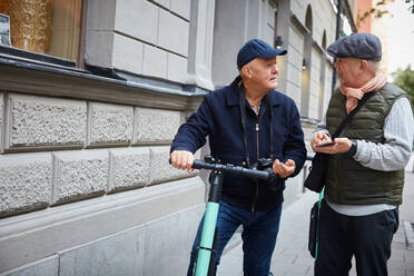 Senior gay couple using push scooters while holding mobile phone in city - MASF17158