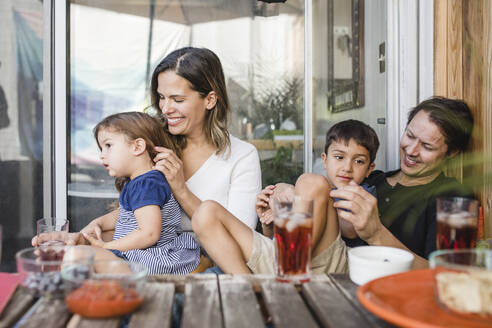 Happy parents sitting with children at table against glass door - MASF17194