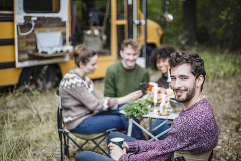 Portrait of smiling man sitting with friends at table during camping in forest - MASF17284