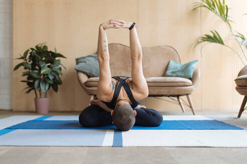Short haired woman practicing yoga lotus pose in home loft interior - CAVF76774