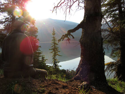 Young man meditating alone by still mountain lake at sunrise - CAVF76846