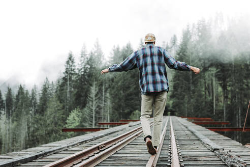 Young man balancing on railroad tracks over bridge in foggy forest - CAVF76966