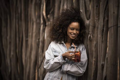 Portrait of happy woman drinking fresh ice tea drink - MJRF00271