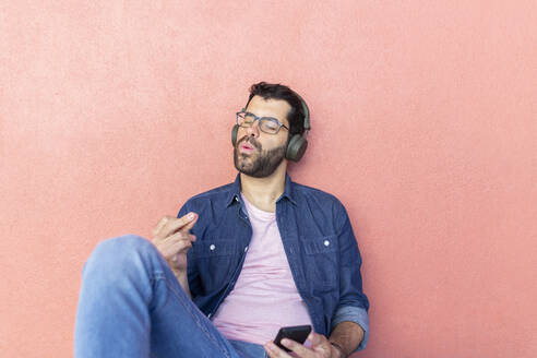 Portrait of whistling man with eyes closed leaning against pink wall listening music with headphones - JPTF00471