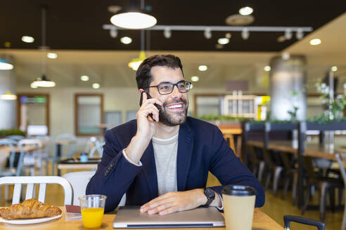 Portrait of happy businessman on the phone in a coffee shop - JPTF00483
