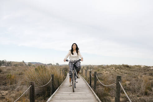 Woman riding bicycle on a boardwalk in the countryside - JRFF04130