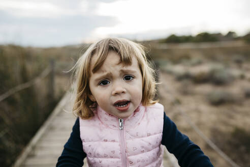Portrait of a sad toddler girl on a boardwalk in the countryside - JRFF04145