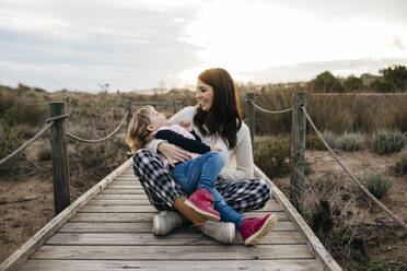 Happy mother and daughter sitting on a boardwalk in the countryside - JRFF04160