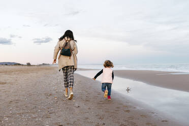 Rear view of mother and daughter running on the beach at sunset - JRFF04181
