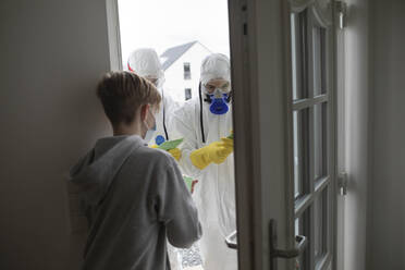 Scientists wearing protective clothing informing people at the door - KMKF01236