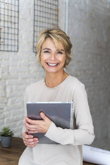 Portrait of smiling mature woman in office holding graphics tablet - AFVF05646