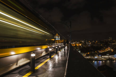 Portugal, Porto, Blurred motion of subway train passing elevated railway track at night - LJF01391