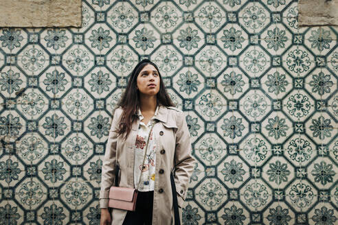 Portugal, Lisbon, Young traveller looking up and standing at a wall with typical Portuguese tiles - DCRF00125