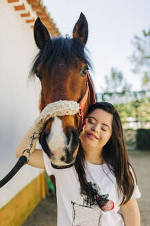 Teenager with down syndrome hugging her horse - DCRF00134