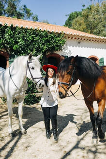 Teenager with down syndrome wearing red hat with two horses - DCRF00140