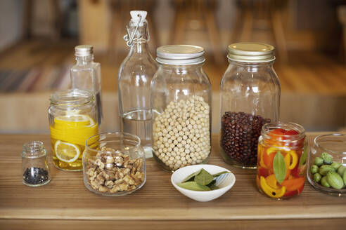 Close up of a selection of condiments and dried pulses in glass jars. - MINF14230