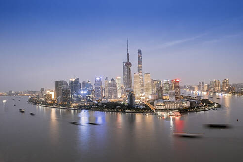 The illuminated skyline of Pudong district in Shanghai with the Huangpu River in the foreground, Shanghai, China, Asia - RHPLF14011