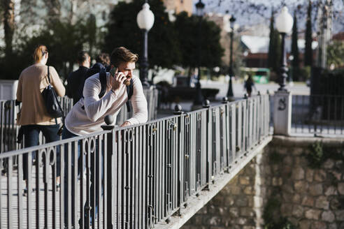 Man on a bridge talking on the phone - LJF01397
