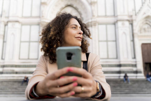 Woman with smartphone at Santa Croce church, Florence, Italy - FMOF00906
