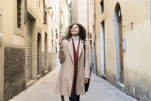 Happy woman eating an ice cream cone in an alley, Florence, Italy - FMOF00924