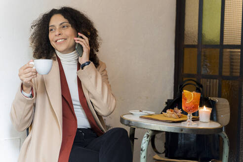 Smiling woman on the phone in a cafe - FMOF00927