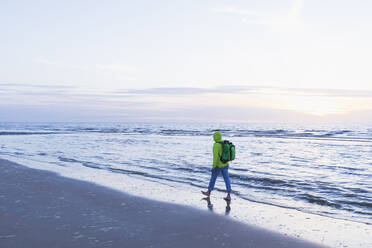 Full length of retired senior man with backpack walking on shore at beach during sunset, North Sea Coast, Flanders, Belgium - GWF06549