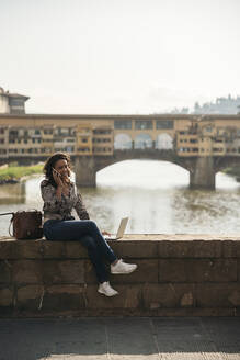 Young woman using laptop and cell phone on a bridge, Florence, Italy - JPIF00446