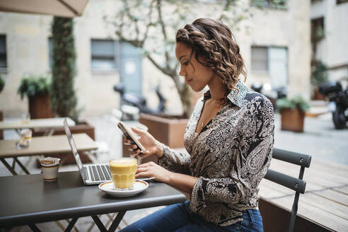 Young woman using laptop and smartphone at a pavement cafe - JPIF00452
