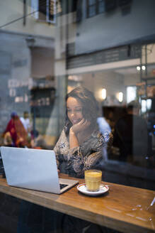 Young woman using laptop in a cafe behind windowpane - JPIF00464