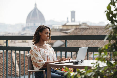 Young woman using laptop on a balcony in Florence, Italy - JPIF00494