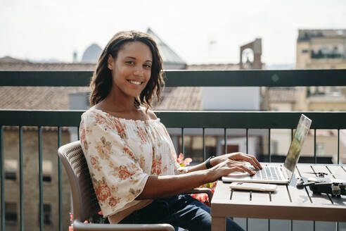 Portrait of smiling young woman using laptop on a balcony in Florence, Italy - JPIF00497