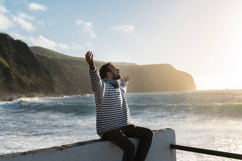 Man sitting at the coast at sunset with outstretched arms, Sao Miguel Island, Azores, Portugal - AFVF05697
