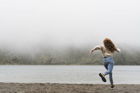Full length of female explorer running at lakeshore in Sao Miguel Island, Azores, Portugal - AFVF05716
