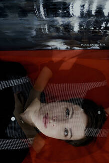 Portrait of a short-haired woman lying down beside painting - OGF00247