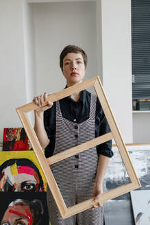 Portrait of a female painter holding a picture frame in her studio - OGF00250