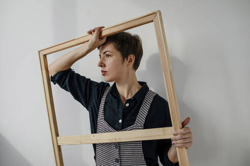Portrait of a female painter holding a picture frame in her studio - OGF00256