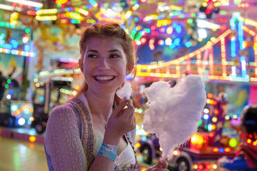 Portrait of happy redheaded teenage girl with candy floss at Oktoberfest - LBF02952