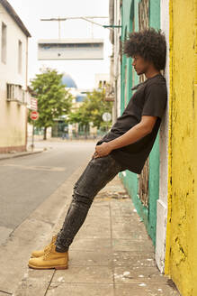 Young man with afro leaning against wall in the city - VEGF01755
