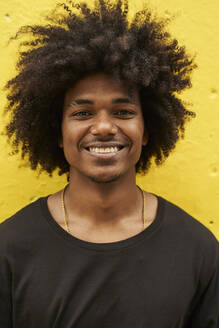 Portrait of happy young man with afro against yellow wall - VEGF01761