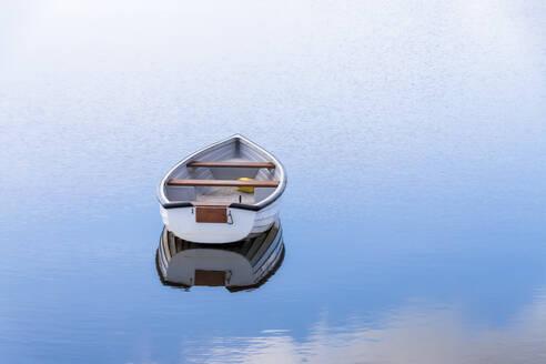 UK, Scotland, Empty rowboat floating in shiny lake - SMAF01862