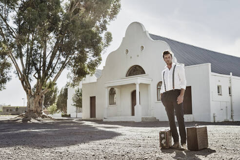 Portrait of man in old-fashioned clothes with suitcases in the countryside - RORF02022