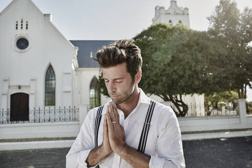 Portrait of man in old-fashioned clothes in the countryside praying at a church - RORF02031
